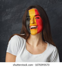 Portrait of happy woman with the flag of Belgium painted on her face. Football or soccer team fan, sport event, faceart and patriotism concept. Studio shot at gray background, copy space
