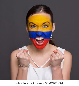 Portrait of happy woman with the flag of Columbia painted on his face. Football or soccer team fan, sport event, faceart and patriotism concept. Studio shot at gray background, copy space