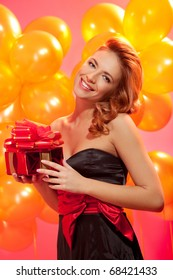 portrait of happy woman with gift box over pink background