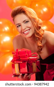portrait of happy woman giving a gift box over pink background