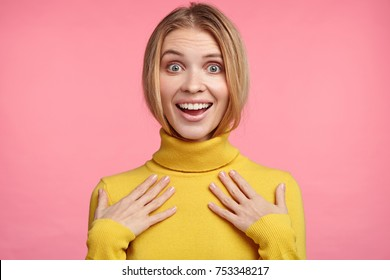 Portrait of happy woman glad to recieve new sweater as present from husband, tries it on, looks in mirror, likes color and style, has joyful expression. Amzed female model in yellow polo neck sweater