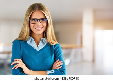Portrait of happy woman  with glasses in business center with crossed hands