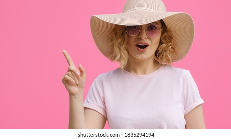 Portrait of happy woman in hat, pink sunglasses with finger shows place for your advertising product joy on pink background. Monotone. Emotions of people. Life style. Positive. Copy space