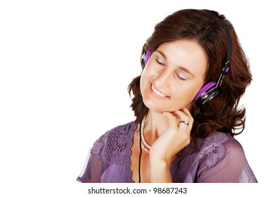 portrait of a happy woman in her 30s listening to music with earphones over white background with space for text