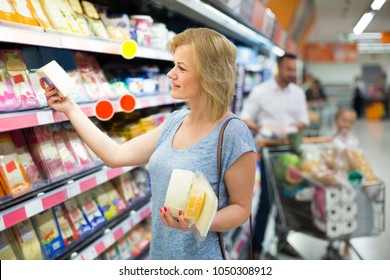 Portrait of happy woman holding assortment of cheese in grocery shop