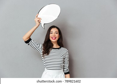 Portrait of a happy woman holding blank speech bubble above her head isolated over gray background