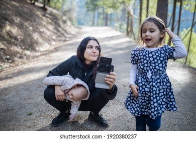 Portrait of happy woman holding her adorable baby in the woods next to her older daughter. Mother hugging cute baby and squatting on path with blurry trees as background. Young family in forest