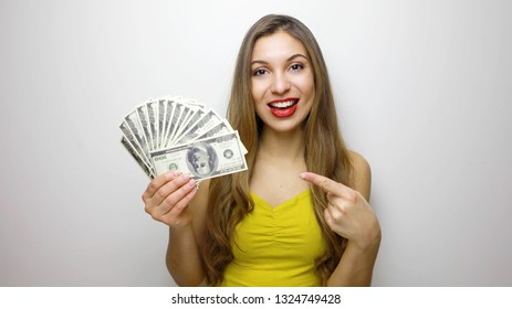 Portrait of happy woman holding and pointing finger fan of money isolated over white background