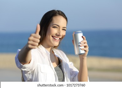 Portrait of a happy woman holding a refreshment can looking at you on the beach