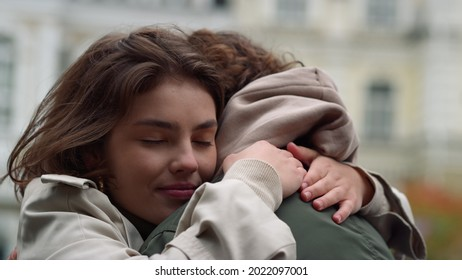 Portrait of happy woman hugging man in city center. Love couple spending time together in old town. Affectionate boyfriend and girlfriend having romantic date on urban street.