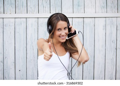 Portrait of a happy woman listen music with thumbs up