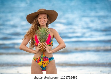 Portrait happy woman with long blonde curly hair holding pineapple on the beach with enjoying and refreshing, summer beach relaxing time concept.
