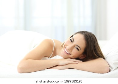 Portrait of a happy woman looking at camera lying on a bed in the morning