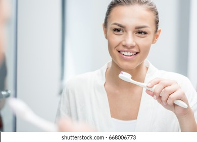 portrait of happy woman looking in mirror while brushing teeth in morning
