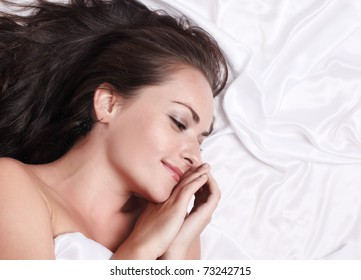 Portrait of happy woman lying on white silk bed, closeup.