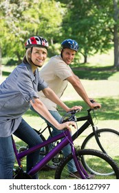 Portrait of happy woman with man cycling in park