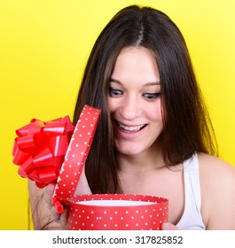 Portrait of happy woman opening gift box against yellow background