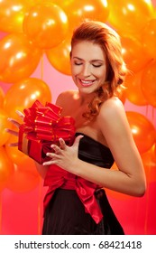 portrait of happy woman opening gift box over pink background