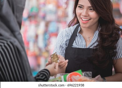 portrait of happy woman paying her shopping with credit card in grocery store