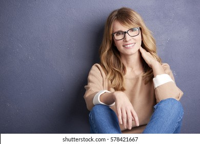 Portrait of a happy woman posing against a a grey background while lying against the wall.