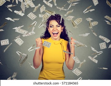 Portrait happy woman pumping fists ecstatic celebrates success under a money rain falling down dollar bills banknotes isolated on gray wall background with copy space