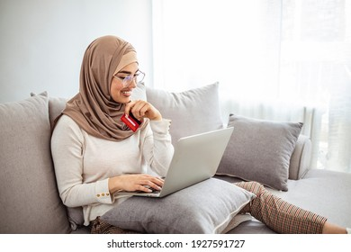 Portrait of happy woman purchasing product via online shopping. pay using credit card. Beautiful young muslim woman with credit card and laptop smiling. Online Credit Concept