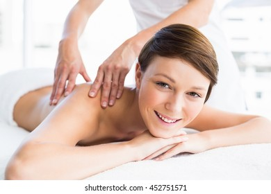 Portrait of happy woman receiving back massage from masseuse at spa