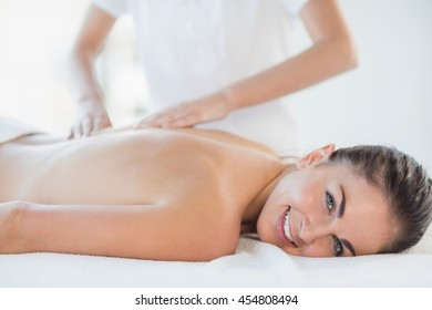 Portrait of happy woman receiving back massage at spa