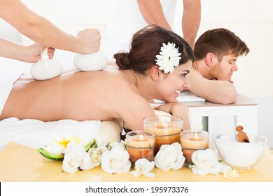 Portrait of happy woman receiving massage with herbal compress stamps on back at spa