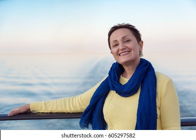 Portrait of happy woman relaxing on a luxury cruise liner boat. Beautiful sunset or sunrise blurred background. Summer vacation trip concept.