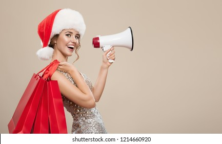Portrait of happy woman in santa hat holding red shopping bags. Shout into megaphone on copyspace.