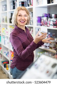 Portrait of happy woman selecting face cream in beauty store