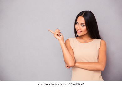 Portrait of a happy woman showing finger away over gray background