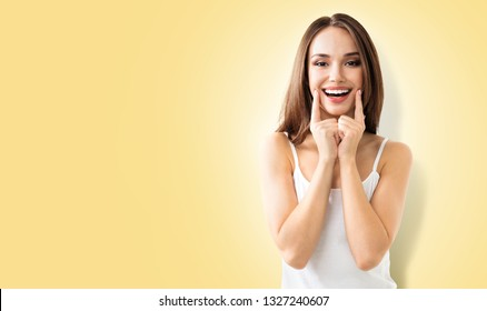 Portrait of happy woman showing smile, in casual smart clothing, against yellow color background, with blank copy space area, for some text, advertising or slogan