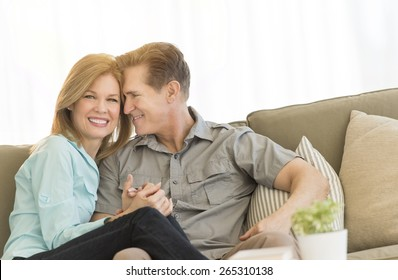 Portrait of happy woman sitting with loving man on sofa at home
