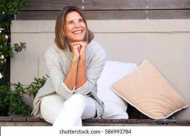 Portrait of happy woman sitting outside looking away