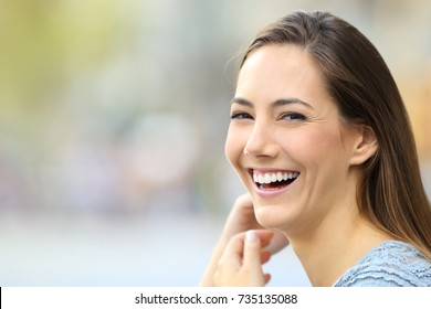 Portrait of a happy woman smiling looking at camera on the street