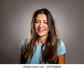 portrait of happy woman smiling on a gray background
