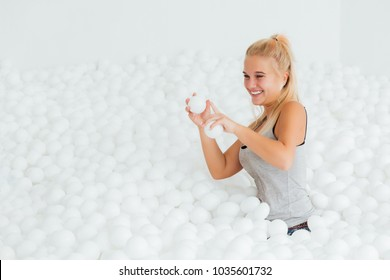 Portrait Happy woman stand surrounded by white plastic balls in the dry pool. Copy splace. Adult childhood at Playground with pit-ball. She swung to throw the ball.