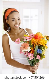 Portrait of happy woman standing with flower bouquet handheld, smiling at camera.?