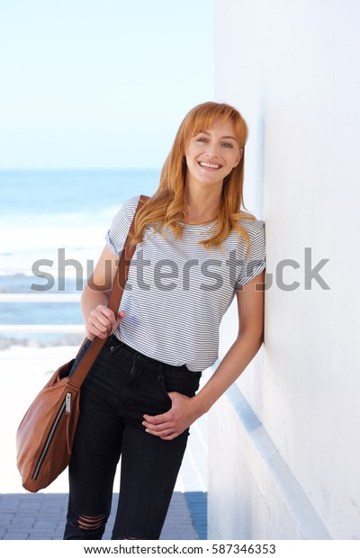 Portrait of happy woman standing with purse with sea in background
