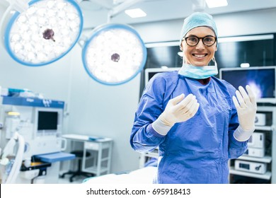 Portrait of happy woman surgeon standing in operating room, ready to work on a patient. Female medical worker in surgical uniform in operation theater.