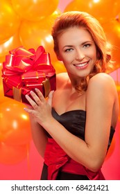 portrait of happy woman trying to guess what is in the gift box over pink background