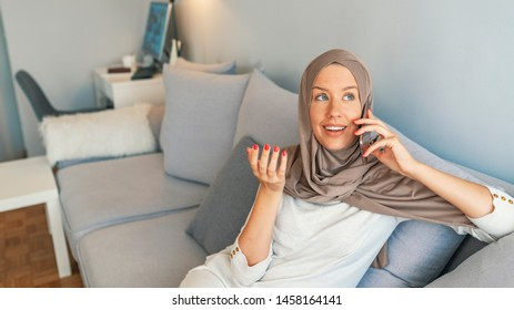 Portrait of happy woman using mobile phone while sitting on a couch. Portrait of a smiling beautiful muslim woman texting with her smartphone while sitting on a couch at home