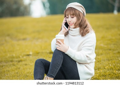 Portrait of a happy woman using smart phone in a park