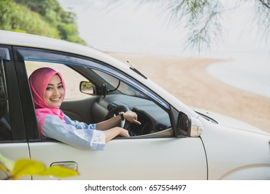 portrait of happy woman wearing hijab travelling with a car to the beach on summer holiday