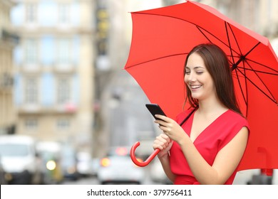 Portrait of a happy woman wearing red blouse texting on a smart phone under an umbrella in a rainy day in the street of an old town