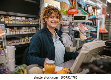 Portrait of a happy woman working at checkout counter smiling at camera. Supermarket employees working at cash register counter.