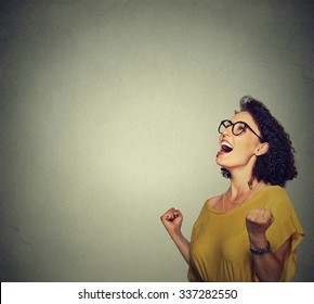 portrait happy woman in yellow dress exults pumping fists ecstatic celebrates success