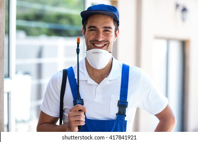 Portrait of happy worker with crop sprayer standing in back yard